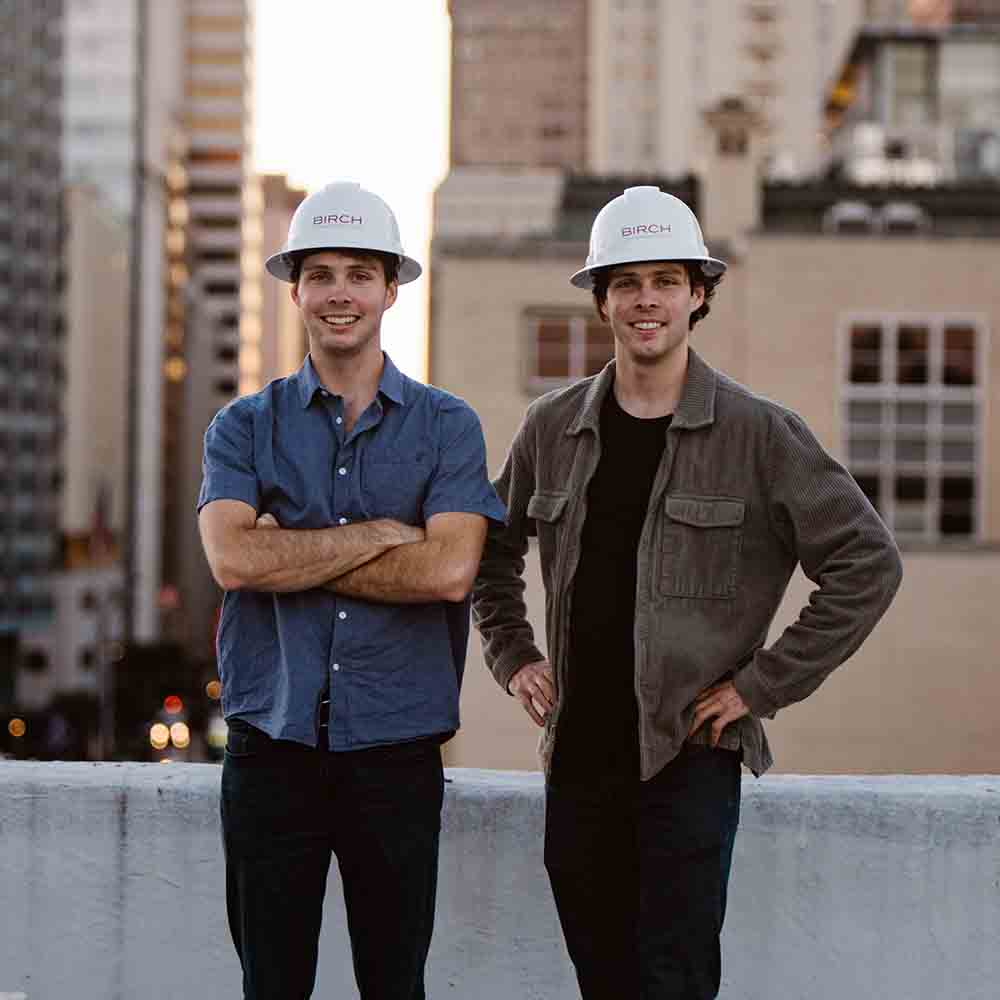 Founders of SOVA wearing hard hats and smiling