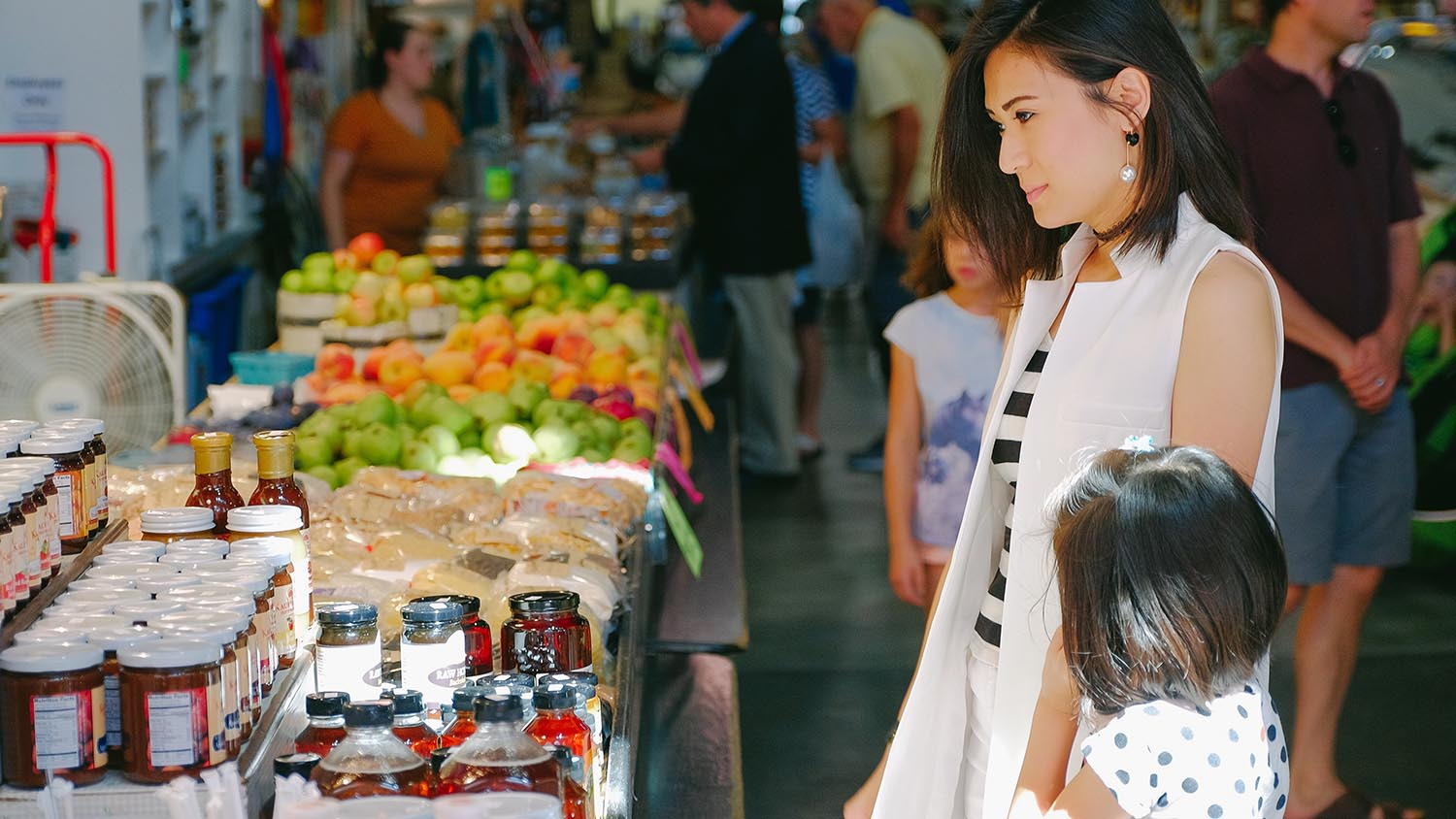 A young woman and her child shopping at a farmers market