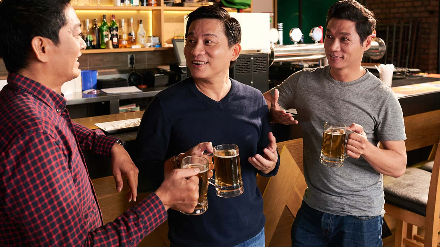 Three men drinking beer and talking at a brewery