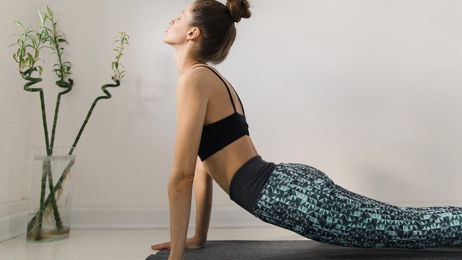 A young woman doing yoga inside